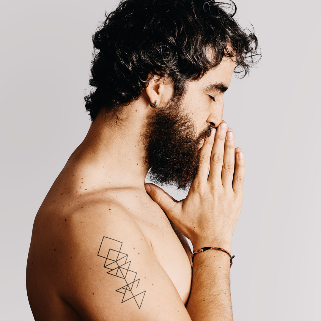 Men with a abstract runes word shoulder tattoo by Discreet Tattoos