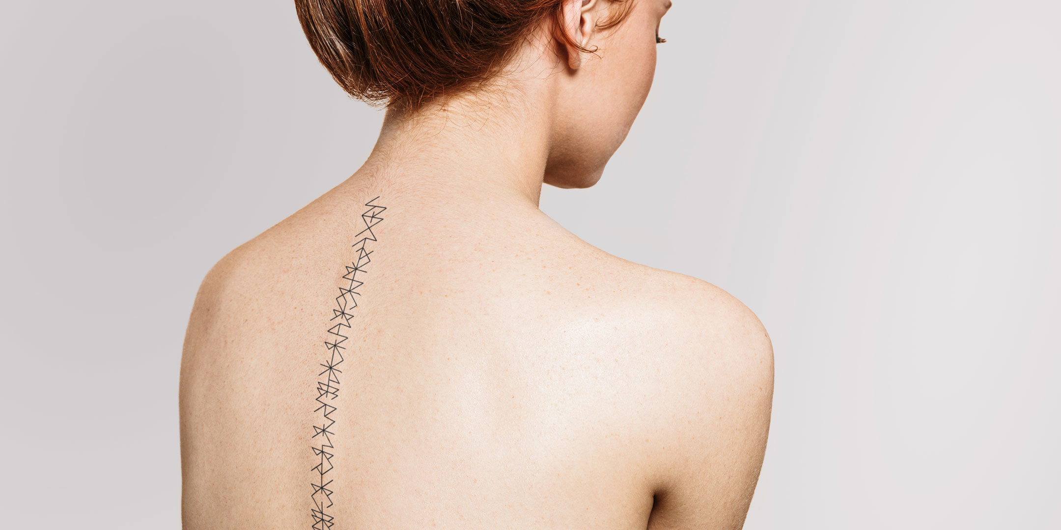 abstract words along back spine by Discreet Tattoos